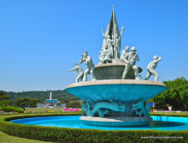 A light stone fountain depicting soldiers from the Korean War, on a sunny day, with blue water surrounding it, green grass and trees in the background.