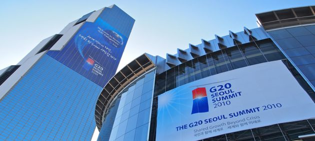 Looking up at a tall glass skyscraper on the left of the frame, and on the right a circular glass building, with large signs announcing the G20 summit in Seoul.