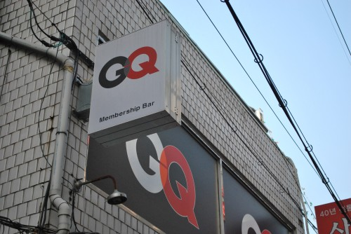 A white tiled exterior of a building showing a close up of a sign to a membership bar, in black and red.