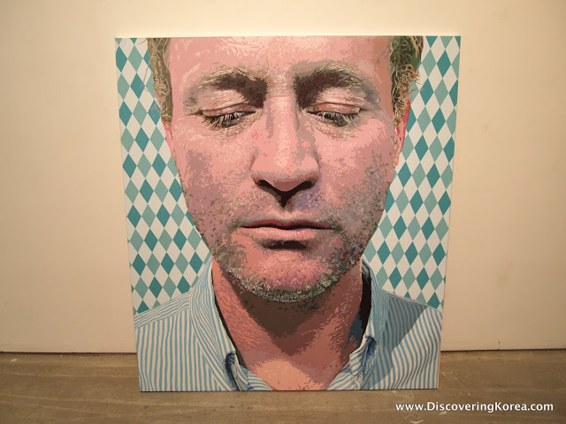 An art piece at Gallery LVS, a close up painting of a man's face, eyes looking down on a green and white checkered background. The painting leans up against a cream wall and rests on a wooden floor.