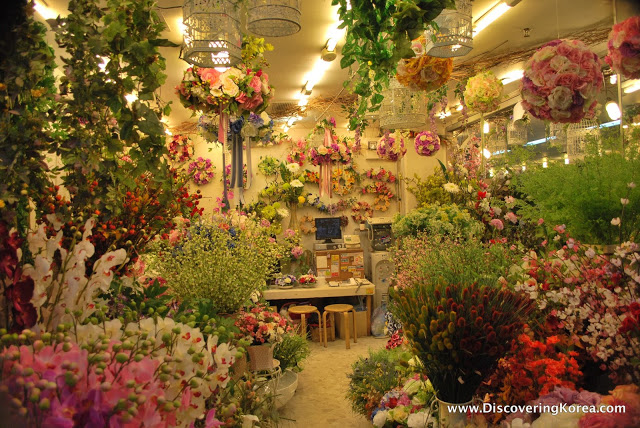 A flower stall at Gangnam shopping arcade, filled with orchids and other brightly colored flowers and foliage.