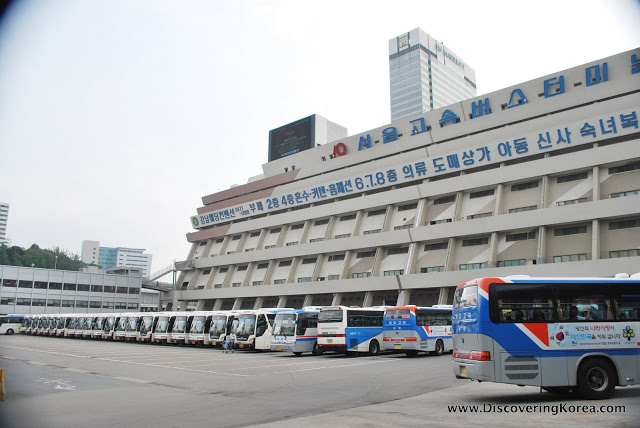 A large white building with Korean lettering on the outside, Gangnam shopping arcade, with a long line of tour buses parked on the concrete outside.