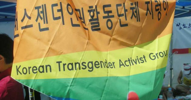 A yellow, orange and green flag, with Korean lettering at the top of the frame, and english signage below.