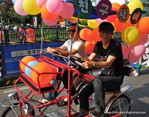 Two men on a bicycle rickshaw, with balloons drive through Seoul's streets at the Queer Culture parade.