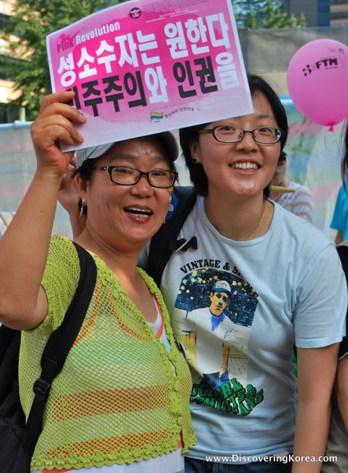 Two women pose for the camera, dressed in t shirts, both wearing glasses, one is holding up a pink banner with white and black Korean lettering.