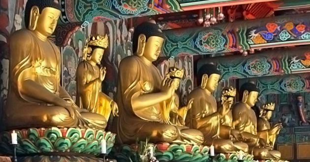 Gold statues of Buddhist monks praying, at Geumsansa temple, with green, purple, red and gold paint effects on the walls and the ceiling.