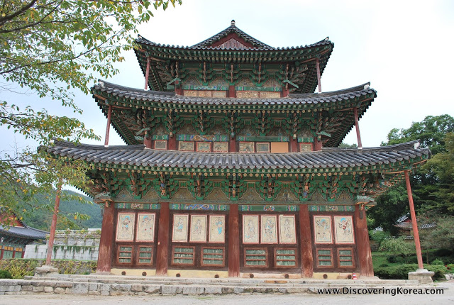 Geumsansa Gold Mountain Temple, a three story wooden building with ornate carving painted in turquoise, with red pillars.