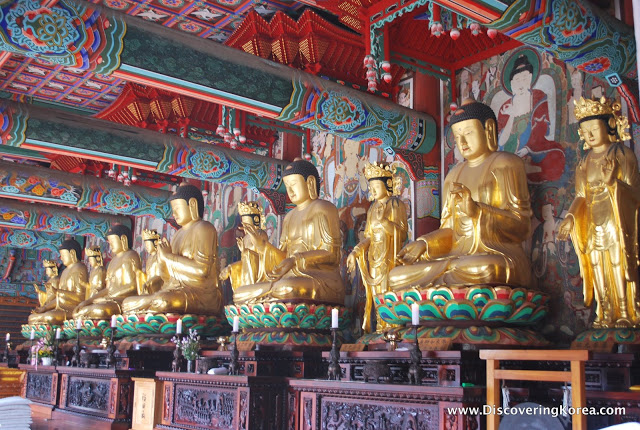Gold states of Buddhist monks, seated in prayer, intricately painted walls and ceiling in turquoise, red, orange. Each statue is seated on a carved wooden plinth.