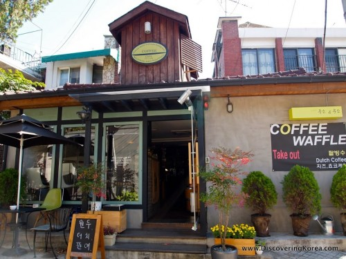 Exterior of a coffee shop in Seoul, a wooden building with seating outside, ornamental trees in pots, and a chalkboard sign with Korean lettering.