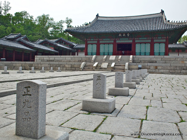 The view towards the entrance to Gyeonghuigung summer palace, showing the stone work, and elaborate green fretwork on the outside of the dark red building.