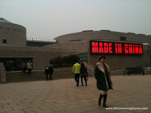 Exterior image of Gwacheon museum, with a red and black sign, and pedestrians in the foreground.