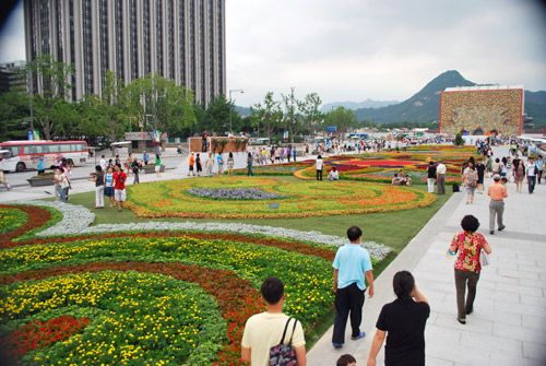 A large multicolored flower carpet as part of Gwanghwanun Square, circular plantings of different colored flowers with stone walkways down either side, with pedestrians, against a backdrop of a large building and a mountain in the distance.