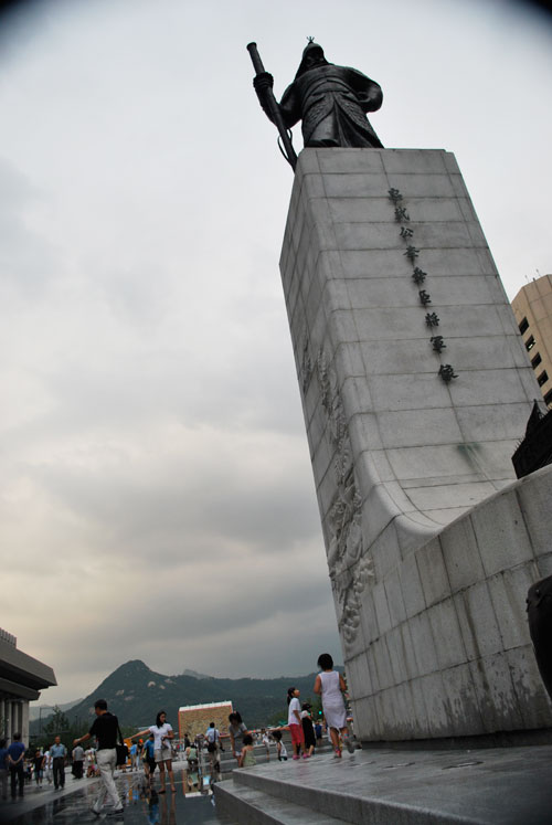 To the right of the frame is a tall concrete plinth with a statue on top of it, to the left are pedestrians on a street with no cars, the background is gathering clouds and a mountain in soft focus.