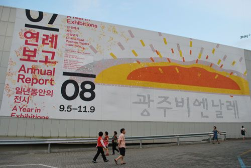 A large billboard, in white with red and black writing, and a red and orange picture, with pedestrians walking in the foreground.
