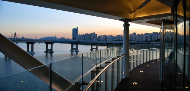 View across a river from a bridge with a glass and metal railing, towards the city of Seoul, in evening light.
