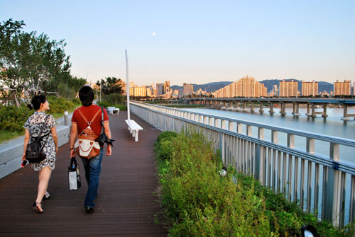Two people walking over the Gwangnaru pedestrian bridge, with metal railings to the right of the frame, and some low bushes, to the left of the frame are trees and ahead is the city of Seoul in evening light.