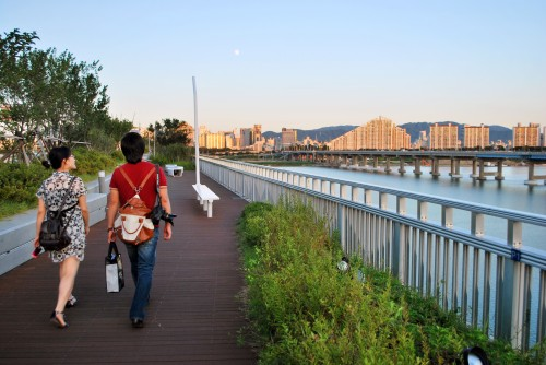 A man and a woman walking across Gwangnaru pedestrian bridge, with the river to the right of the frame, and cityscape behind.