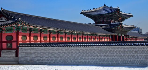 Outside view of Gyeongbokgung, showing a tiled wall, and red siding. Turquoise and red ornate eaves.