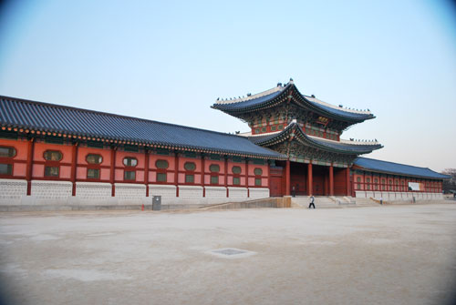 The light red exterior of Gyeongbokgung, showing an ornate two story entrance way, with dark roofing, and a stone colored area in front.