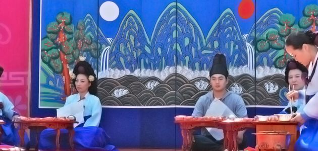 Four traditionally-dressed people sitting at low tables at Gyeonhuigung with a blue mural in the background depicting mountains and trees.