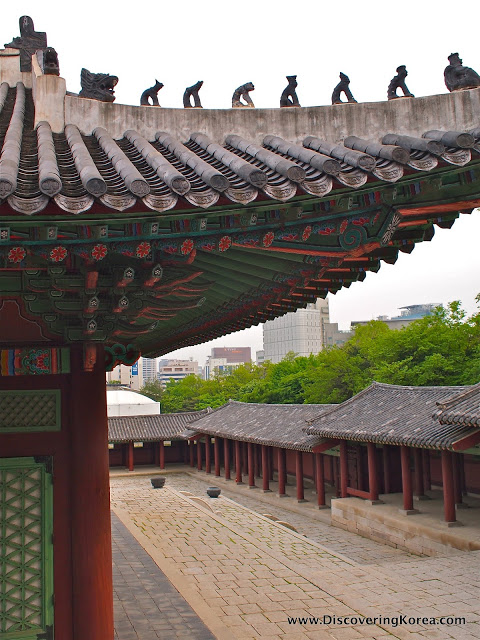 Close up of green and red ornate detail on the roof eaves of Gyeonghuigung summer palace.