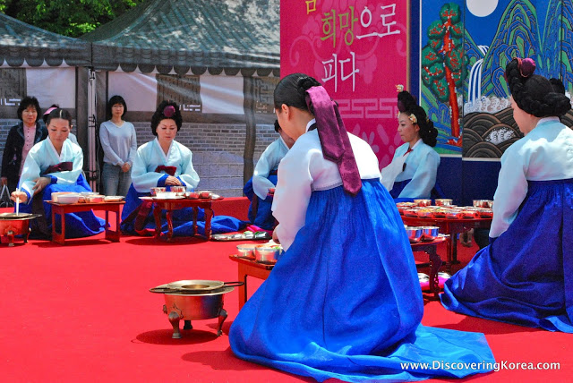 Six traditionally-dressed Korean ladies, in blue, kneel in front of low tables on a red surface. In the background are two observers.