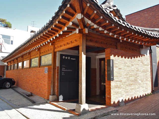 Red brick building housing the Hakgojae gallery. Ornate roof, and a pillar in the doorway. To the left is a parked car.