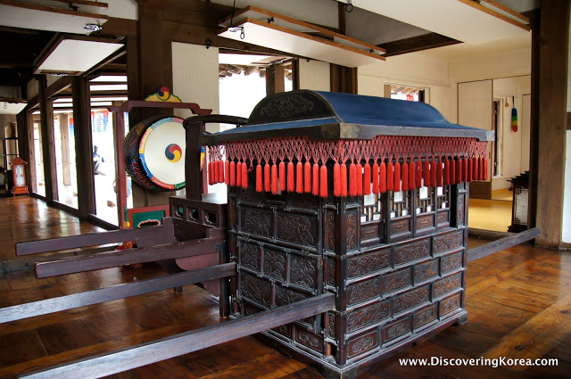 A dark wooden hand cart, with ornate carving in the wood, and red tassels around the top. The background is of the inside of a building, with a wooden floor and white walls.