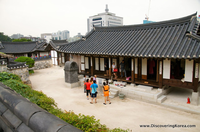 A traditional hanok at Namasangol village. White and brown wooden building, with stone steps, a dark roof and visitors in a group. In the background is a modern tower block and another hanok to the left of the frame.