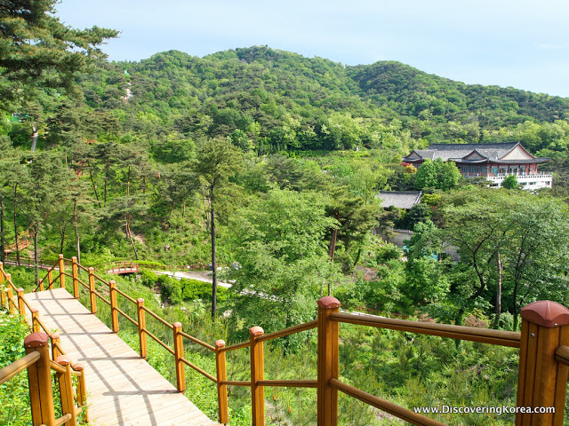A boardwalk heading downhill into the forest at Seoul fortress, with a house to the left of the frame.