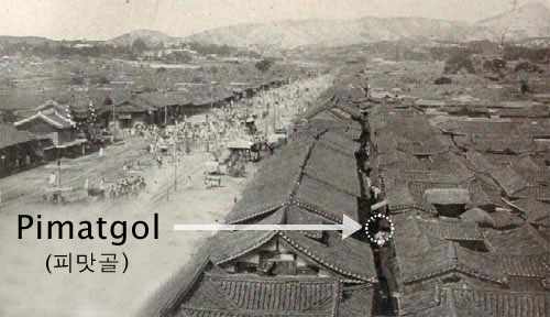 A historical photo of old Seoul, with the river running in the center of the frame and lots of small traditional houses with curved roof. Black text points to a small area between the houses.