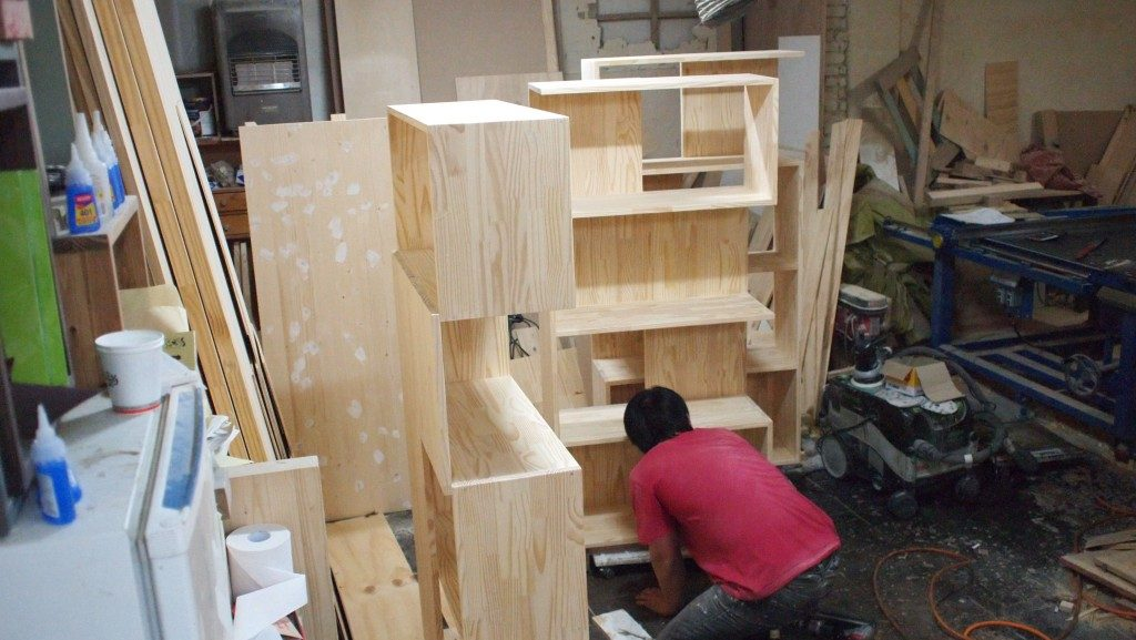A man in a red shirt, kneeling down with a stripped pine cabinet he's working on in front of him. In the background are various tools and pieces of wood in the furniture workshop at Hongdae.