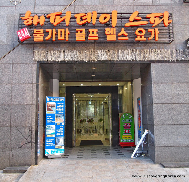 Exterior view of Hongdae spa, with a Korean sign in orange over a glass door, a menu of spa treatments in Korean is to the left. The background is a concrete block building.