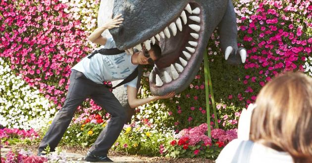 A young man leans into the mouth of a model dinosaur, putting his head between the sharp teeth, while a woman in the right of the frame takes a photograph. The backdrop is pink and white flowers in bright sunshine.
