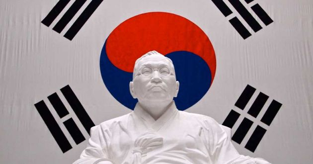 White statue of a Korean man, on a white background, with a red and blue yin-yang symbol behind and four black symbols consisting of parallel lines.
