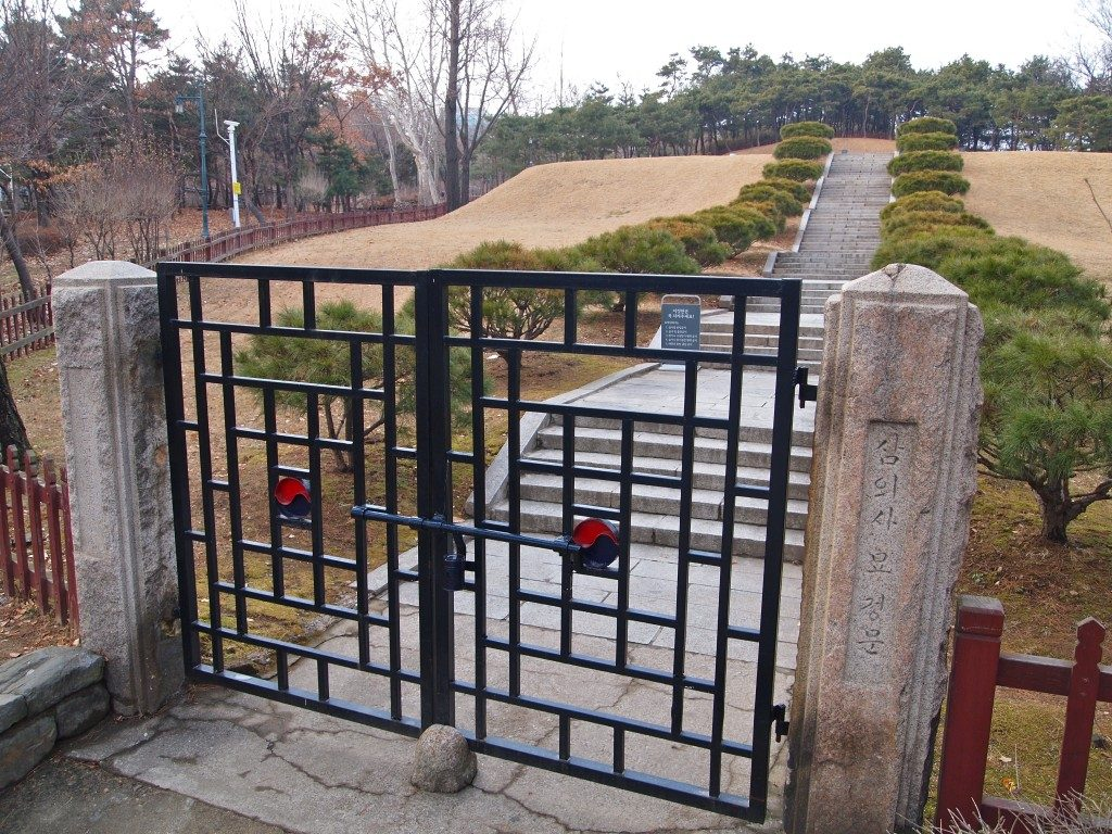 Black metal gates, set between carved stone posts at the entrance to Hyochang park, with stone steps leaving up in between low bushes with grass in the background.