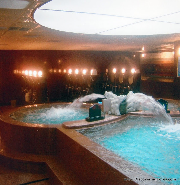 Two spa pools with water fountains emptying into them. The left side one is circular, and the right square. The background shows a skylight above the pools, and lights.