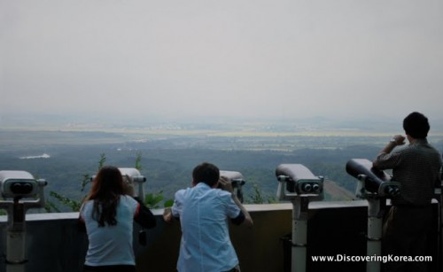 Tourists pictured taking photographs and viewing through binoculars over DMZ.