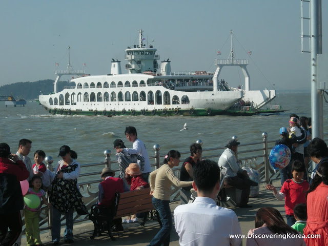 A large passenger ferry in the water, approaching Incheon port. Pedestrians in the foreground.