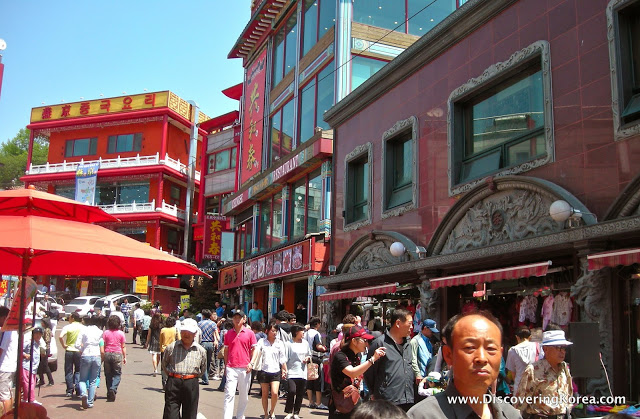 Street scene in Incheon, with red buildings in the background and pedestrians.