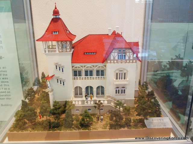 Scale model of a white building with a red roof inside a glass case.