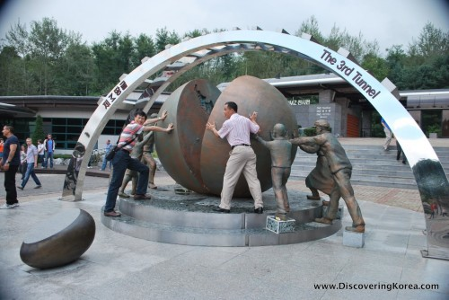 The 3rd infiltration tunnel picturing men pushing a bronze statue of a sphere cut in half.