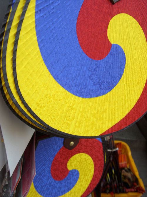 A close up of a Korean fan, in yellow blue and red.