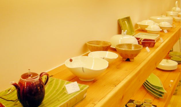 Wooden shelves containing ceramic items, some bowls, a tea pot, serving dishes against a yellow background.