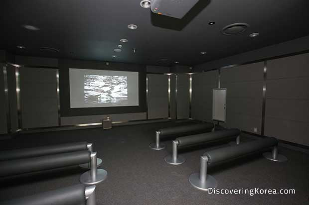 Interior of a screening room, dimly lit with a television on the far wall, and metal bench seating.