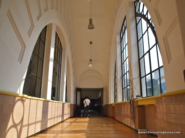 Hallway with wooden floors, and arched windows in stone walls, inside the high-ceilinged Seoul Culture station.