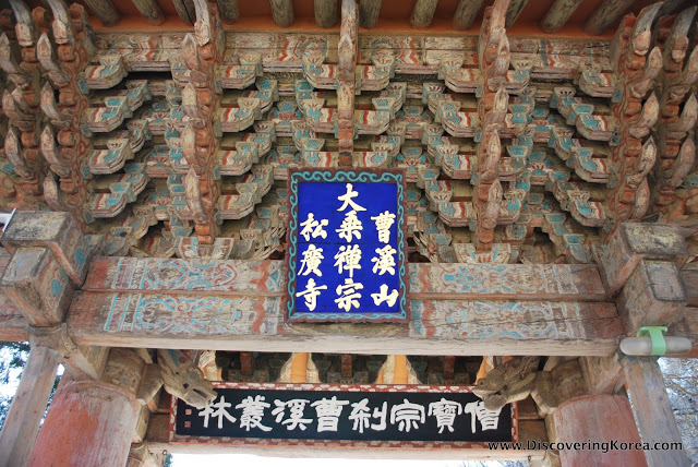 Faded paint on wood carvings in Songgwangsa temple, to the center of the frame is a blue sign with white Korean lettering.