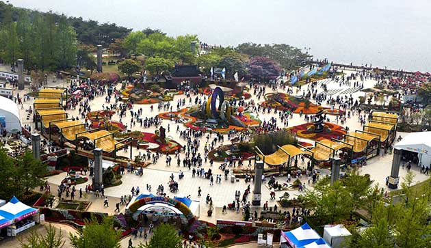View of the international horticulture Goyang in Korea, a show ground with crowds looking at various displays of flowers and landscaping.