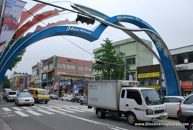 A street in Itaewon, Seoul, showing a blue and red archway over the street with cars and trucks and shopfronts in the background.