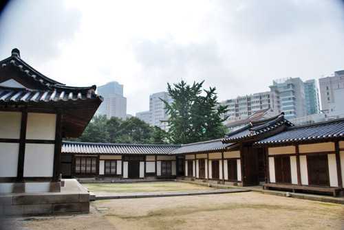 A traditional Korean building built around a courtyard, wooden frame and white walls, with a traditional curved roof. In the background are the modern buildings of Seoul.